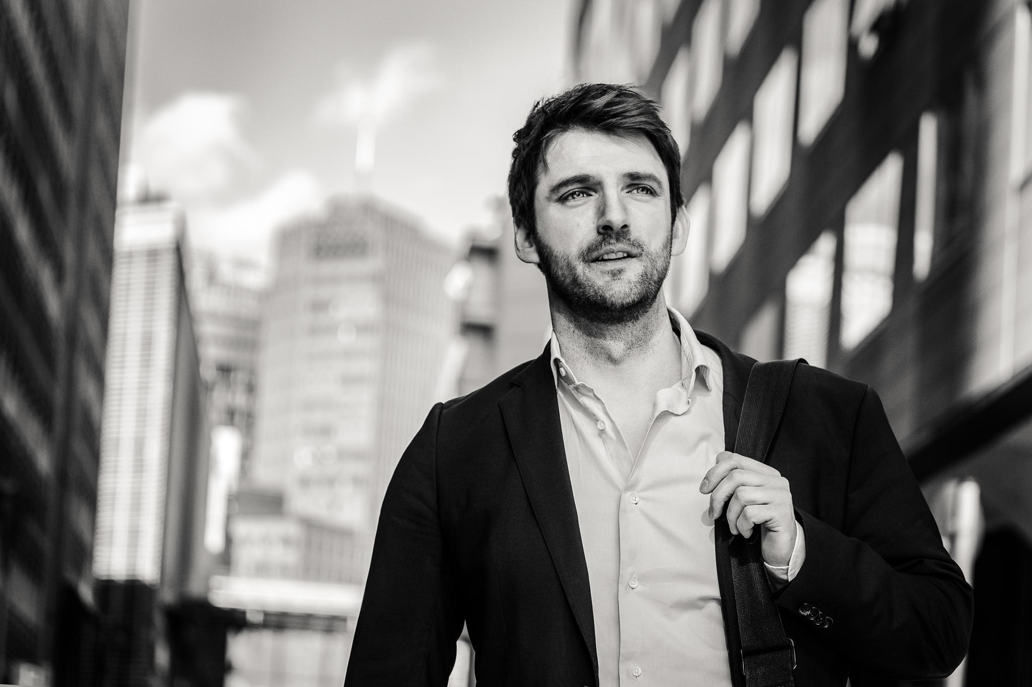 Schwarzweißbild von Martin Geuer im Anzug und Umhängetasche im Zentrum von Berlin