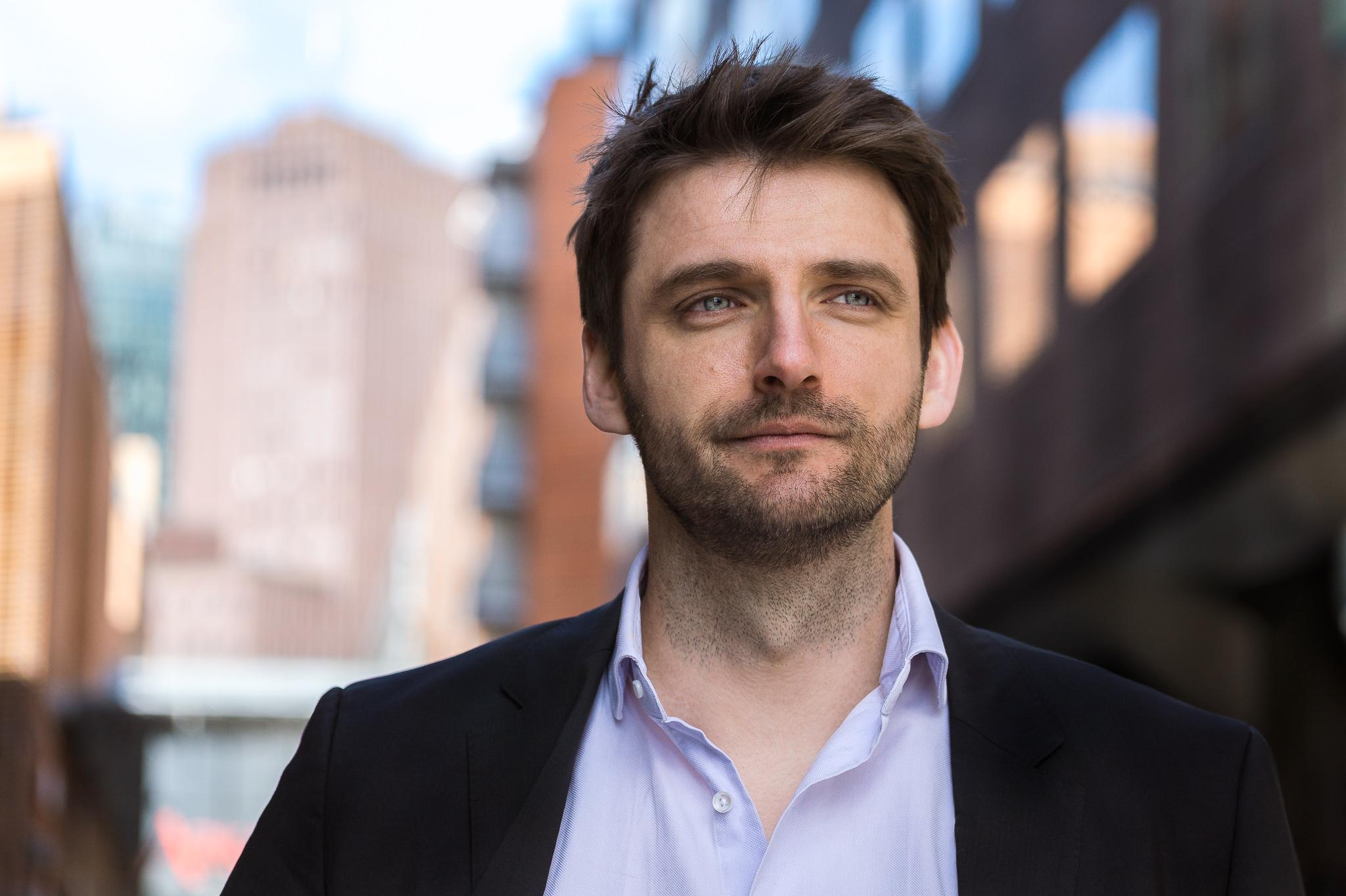 Portrait von Martin Geuer im Anzug mit Hausfaßade im Hintergrund