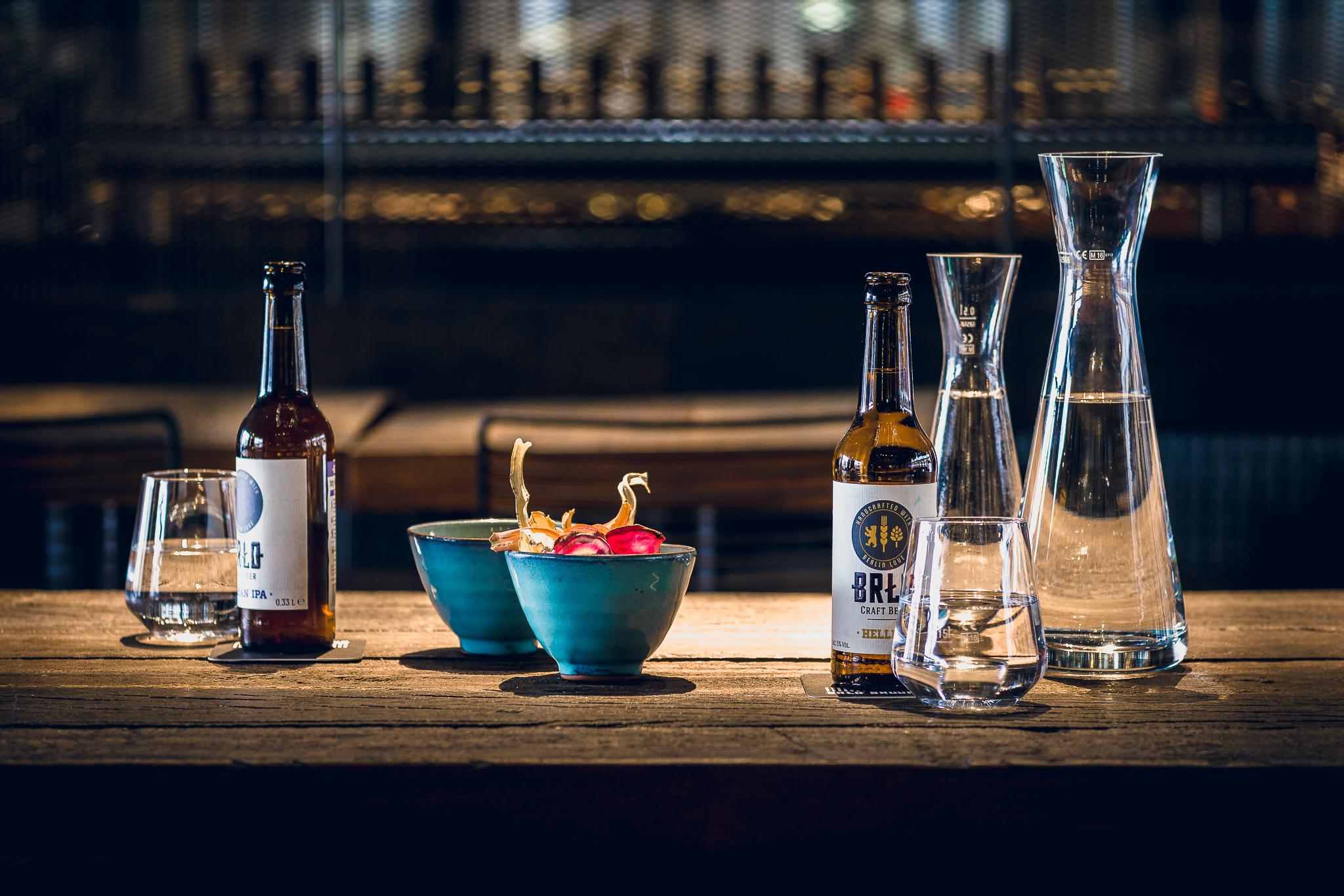 Ein von BRLO Brwhouse gedeckter Tisch mit Bierflaschen, Wasser und gesunden Snacks