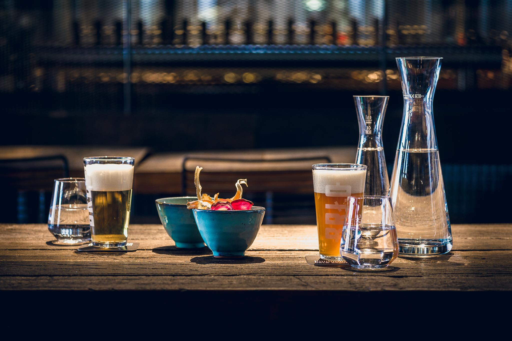 Ein von BRLO Brwhouse gedeckter Tisch mit Bier im Glas, Wasser und gesunden Snacks